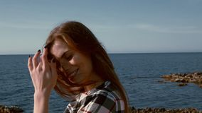 O retrato da mulher bonita na praia pelo vento do oceano funde filme