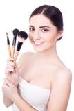 O retrato da mulher bonita nova com compõe as escovas isoladas Fotografia de Stock