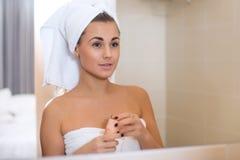 O retrato da mulher com a toalha na cabeça que toca em sua cara refletiu no espelho Fotografia de Stock Royalty Free