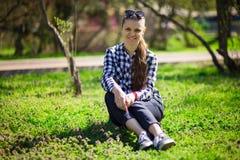 O retrato da mulher consideravelmente alegre descansa no prado verde foto de stock