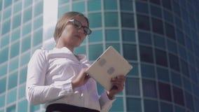 O retrato da mulher de negócio louro nova atrativa que olha em sua tabuleta e vê as fotos filme