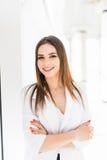 O retrato da mulher de negócio nova segura com braços cruzou a inclinação contra a janela no escritório Fotos de Stock Royalty Free