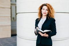 O retrato da mulher de negócios com cabelo encaracolado, vermelho pintou os bordos, roupa elegante vestindo, escrevendo em seu li imagens de stock
