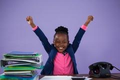 O retrato da mulher de negócios feliz com braços aumentou na mesa Imagem de Stock