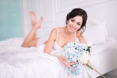 O retrato da mulher elegante com cabelo encaracolado com flores encontra-se na cama Imagem de Stock