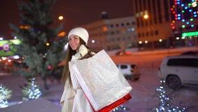 O retrato da mulher feliz após a compra na cidade no Natal decorou ruas, movimento lento Compra bonita da mulher vídeos de arquivo