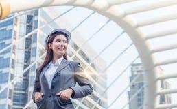 O retrato da mulher nova bonita do coordenador veste um capacete de seguran?a branco que sorri com compromisso ao sucesso na baix imagens de stock