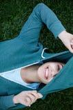 O retrato da mulher nova e desportiva no sportswear encontra-se na grama no parque imagens de stock royalty free
