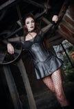 O retrato da mulher sedutor do deathrock do goth vestiu-se na blusa, na saia holey e no espartilho estando entre mecanismos velho Foto de Stock