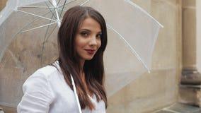 O retrato da mulher smilling nova está com o guarda-chuva em sua mão na rua e a vista na câmera video estoque