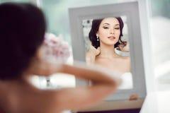 O retrato da noiva bonita nova olha si mesma no espelho fotografia de stock royalty free