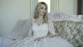 O retrato da noiva bonita senta-se no sofá, sorri-se e olha-se a câmera 4K vídeos de arquivo