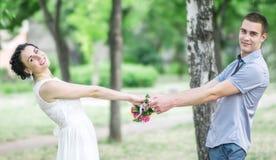 O retrato da noiva fêmea dos pares novos bonitos felizes com casamento pequeno floresce o ramalhete das rosas e o noivo do homem  imagem de stock royalty free