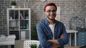 O retrato da posição criativa do homem novo no escritório com braços cruzou o sorriso