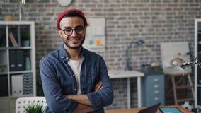 O retrato da posição feliz do proprietário empresarial no escritório com braços cruzou o sorriso