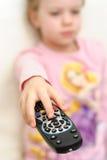 O retrato da rapariga alegre usa o controlo a distância para mudar os canais de televisão Imagens de Stock