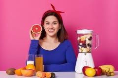 O retrato da terra arrendada fêmea positiva de sorriso cortou o fruto em sua mão O modelo novo espera o batido para estar pronto  foto de stock
