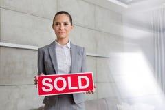 O retrato da terra arrendada nova segura da vendedora vendeu o cartaz contra a parede no apartamento foto de stock