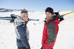 O retrato da vista traseira de um par com esqui embarca na neve Fotos de Stock Royalty Free