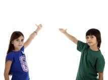 O retrato das crianças felizes aponta acima pelos dedos em algo Foto de Stock