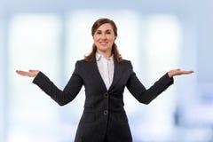 O retrato das orelhas bonitas de uma mulher de negócios 50 velhas nos braços escancarados levanta isolado no branco Foto de Stock