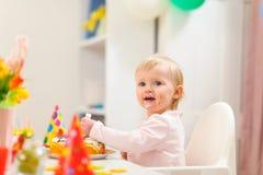 O retrato de come o miúdo manchado que come o bolo de aniversário fotos de stock royalty free