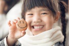 O retrato de crianças bonitas de Ásia sente feliz comendo a cara do smiley do pão fotografia de stock royalty free