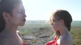 O retrato de dois modelos no vermelho veste-se com ombros desencapados video estoque