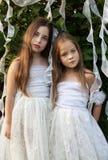 O retrato de duas meninas no branco veste-se no jardim Fotografia de Stock Royalty Free