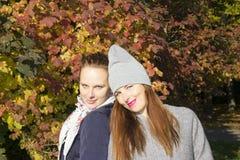O retrato de duas mulheres aproxima a madeira do outono Fotografia de Stock Royalty Free