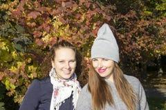 O retrato de duas mulheres aproxima a madeira do outono Fotos de Stock Royalty Free