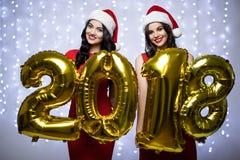 O retrato de duas mulheres no chapéu de Santa e o vestido vermelho com 2018 números no ano novo do og das mãos no bokeh iluminam  imagens de stock royalty free