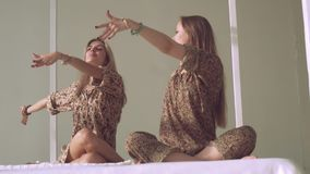 O retrato de duas mulheres novas da ioga que praticam a ioga levanta no estúdio bem iluminado video estoque