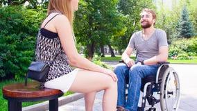 O retrato de jovens felizes desabilita o homem em uma cadeira de rodas video estoque
