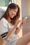 O retrato de meios sociais do bate-papo adolescente bonito da mulher no smrt telefona Imagens de Stock Royalty Free
