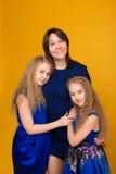 O retrato de meninas bonitas no azul veste-se em um backgrou amarelo imagem de stock royalty free