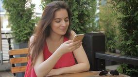 O retrato de messeges de datilografia da senhora do youg em seu smartphone que senta-se no café acolhedor da rua video estoque