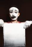 O retrato de mimica guardando a folha suja branca nas mãos Imagens de Stock Royalty Free