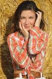 O retrato de mulheres bonitas novas aproxima o monte de feno Imagens de Stock Royalty Free