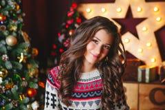 O retrato de mulheres encaracolado de sorriso bonitas aproxima a árvore de Natal celebration imagem de stock