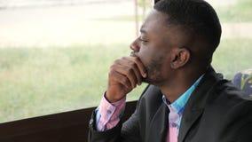 O retrato de olhares novos do homem negro na janela gerencie seus cabeça e olhares na câmera video estoque