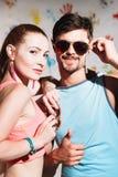 O retrato de pares felizes com polegares levanta o sinal em um fundo positivo engraçado Imagens de Stock Royalty Free