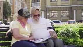 O retrato de pares velhos à moda de viajantes senta-se no banco na cidade estrangeira que olha o mapa vídeos de arquivo