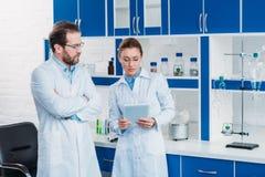 o retrato de pesquisadores científicos no laboratório reveste com a tabuleta digital fotos de stock
