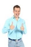 O retrato de rir o homem novo com polegares levanta o sinal foto de stock royalty free