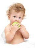 O retrato de um cabelo encaracolado da criança come uma maçã verde Fotos de Stock