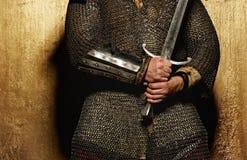 O retrato de um cavaleiro entrega prender uma espada fotografia de stock royalty free