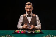 O retrato de um crouoier está guardando os cartões de jogo, jogando lasca-se na tabela Fundo preto imagens de stock royalty free