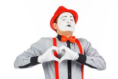 O retrato de um homem, artista, palhaço, MIMICA Mostra um coração isolado sobre imagens de stock