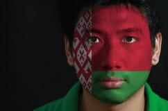 O retrato de um homem com a bandeira de Bielorrússia pintou em sua cara no fundo preto foto de stock